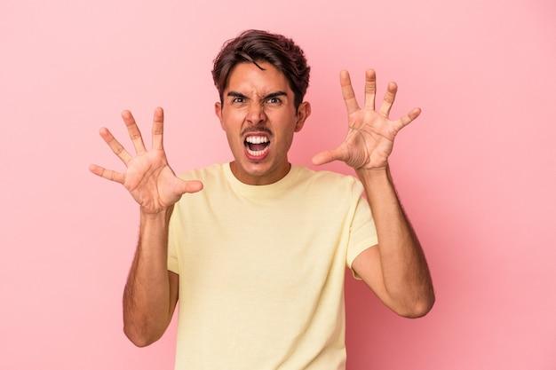 Giovane uomo di razza mista isolato su sfondo bianco che mostra artigli che imitano un gatto, gesto aggressivo.
