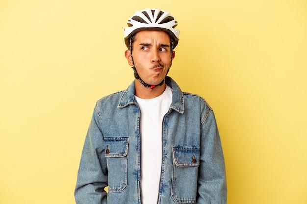 Il giovane uomo di razza mista che indossa una bici da casco isolata su sfondo giallo confuso, si sente dubbioso e insicuro.
