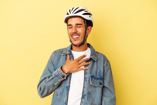 Il giovane uomo di razza mista che indossa un casco da bici isolato su sfondo giallo ride ad alta voce tenendo la mano sul petto.