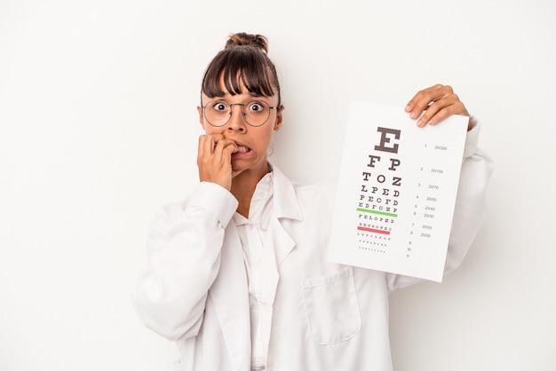 Giovane ottico di razza mista che fa un test isolato su sfondo bianco mangiarsi le unghie, nervoso e molto ansioso.