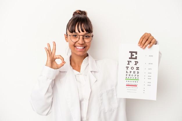 Giovane donna di razza mista ottico facendo un test isolato su sfondo bianco allegro e fiducioso che mostra gesto ok.
