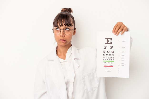 Giovane ottico di razza mista che fa un test isolato su sfondo bianco confuso, si sente dubbioso e incerto.