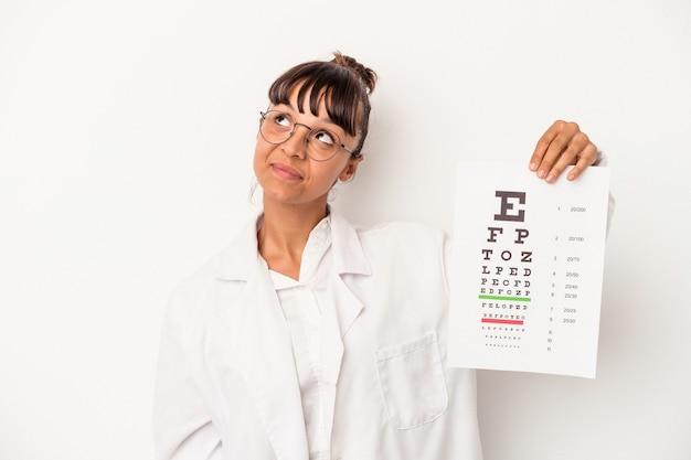 Giovane donna ottica di razza mista che fa un test isolato su sfondo bianco sognando di raggiungere obiettivi e scopi