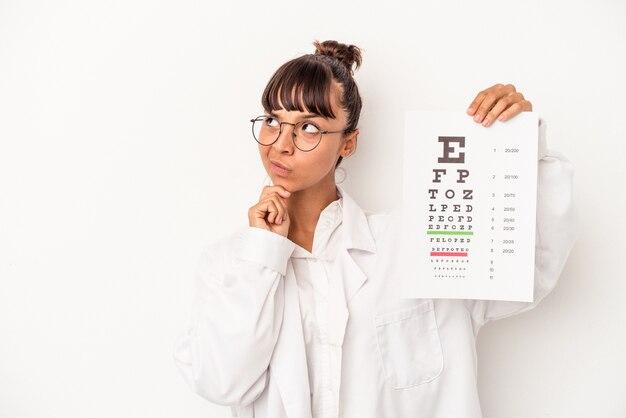 Giovane donna ottica di razza mista che fa un test isolato su sfondo bianco guardando lateralmente con espressione dubbiosa e scettica.