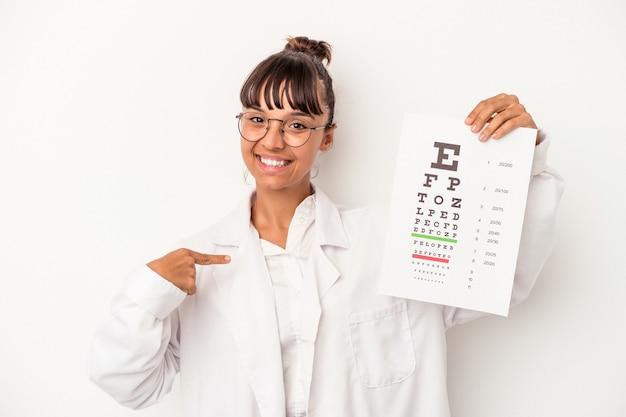 Giovane ottico di razza mista donna che fa un test isolato su sfondo bianco persona che indica a mano uno spazio copia camicia, orgoglioso e fiducioso