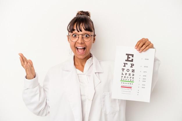 Giovane donna ottica di razza mista che fa un test isolato su sfondo bianco ricevendo una piacevole sorpresa, eccitata e alzando le mani.