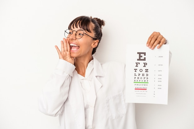 Giovane donna ottica di razza mista che fa un test isolato su sfondo bianco gridando e tenendo il palmo vicino alla bocca aperta.