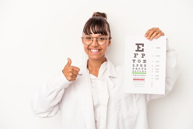 Giovane donna dell'ottico della corsa mista che fa un test isolato su fondo bianco che sorride e che alza pollice su
