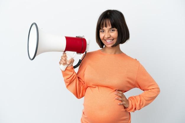 Giovane donna incinta della corsa mista isolata sulla parete bianca che tiene un megafono e che sorride