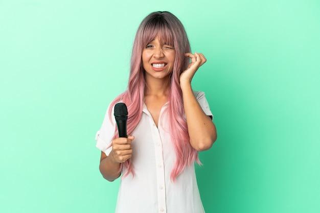 Giovane donna cantante di razza mista con i capelli rosa isolata su sfondo verde frustrata e che copre le orecchie