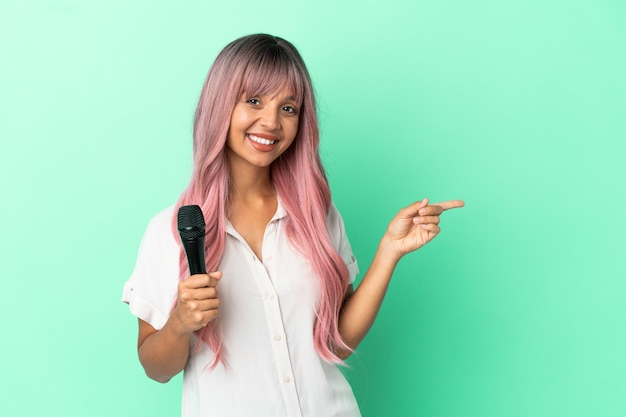 Giovane donna cantante di razza mista con i capelli rosa isolata su sfondo verde che punta il dito sul lato