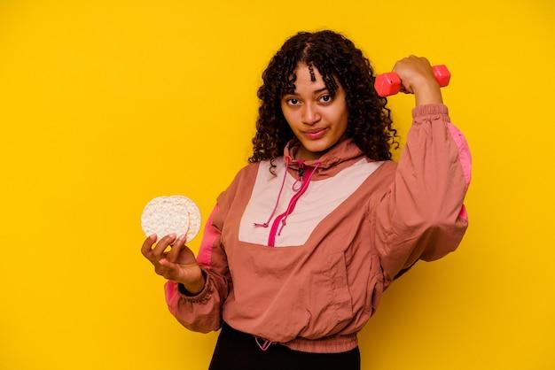 Giovane donna sportiva di razza mista che mangia una torta di riso isolata su priorità bassa gialla