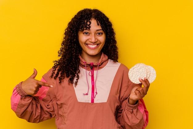 Giovane donna sportiva di razza mista che tiene in mano una torta di riso isolata su una persona gialla che indica a mano uno spazio copia maglietta, orgogliosa e fiduciosa