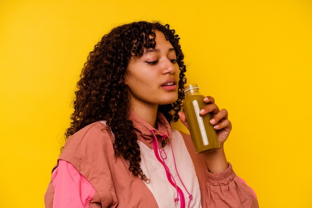 Giovane donna di sport di razza mista che tiene un frullato isolato su sfondo giallo