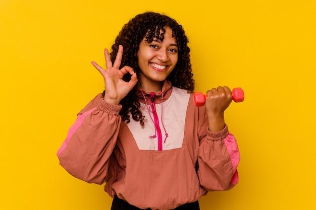 Giovane donna sportiva di razza mista isolata su sfondo giallo