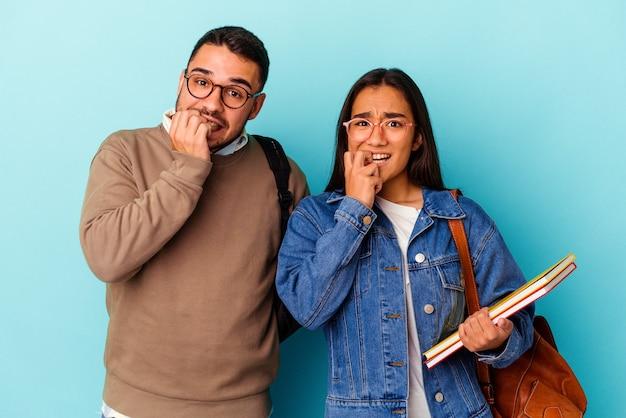 Giovane coppia studentesca di razza mista isolata su sfondo blu che si morde le unghie, nervosa e molto ansiosa.