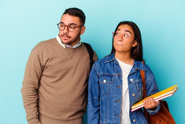 Giovane coppia di studenti di razza mista isolata su sfondo blu confusa, si sente dubbiosa e incerta.