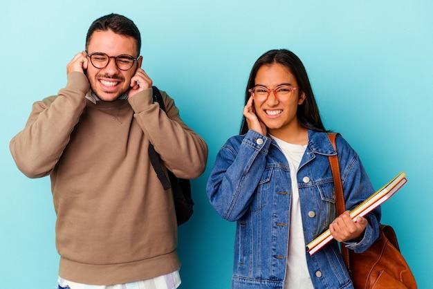 Giovane coppia di studenti di razza mista isolata su sfondo blu che copre le orecchie con le mani.