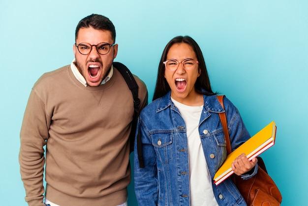Giovane coppia di studenti di razza mista isolata su sfondo blu che urla molto arrabbiato e aggressivo.