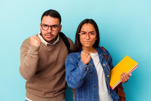 Giovane coppia di studenti di razza mista isolata su sfondo blu che mostra il pugno alla telecamera, espressione facciale aggressiva.