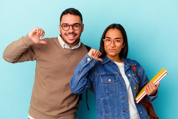 La giovane coppia di studenti di razza mista isolata sul blu si sente orgogliosa e sicura di sé, esempio da seguire.