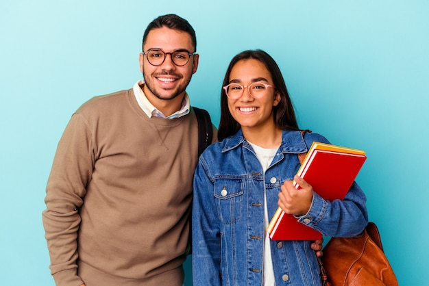 Giovane coppia di studenti di razza mista isolata su blu felice, sorridente e allegra.