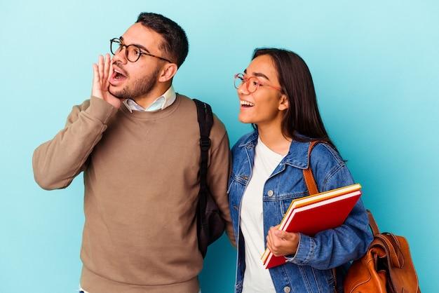 Giovane coppia di studenti di razza mista isolata su grida blu e tenendo il palmo vicino alla bocca aperta.