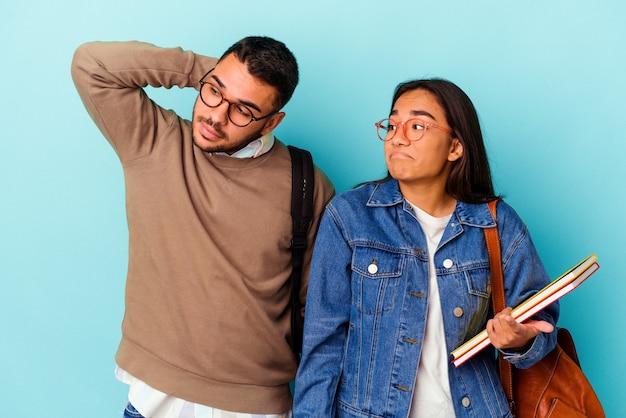 Giovane coppia di studenti di razza mista isolata su blu che tocca la parte posteriore della testa, pensando e facendo una scelta.