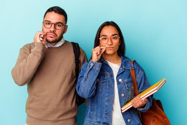 Giovane coppia di studenti di razza mista isolata sul blu con le dita sulle labbra mantenendo un segreto.