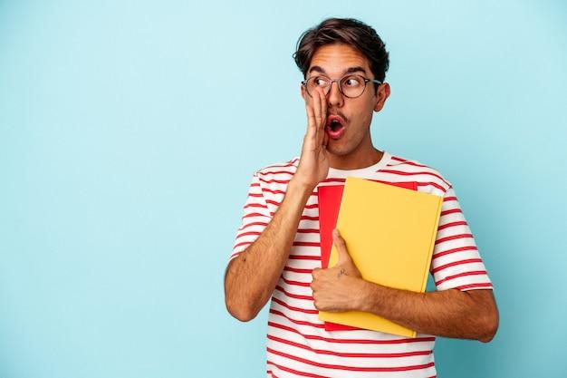 Giovane studente di razza mista che tiene in mano libri isolati su sfondo blu sta dicendo una notizia segreta di frenata calda e sta guardando da parte