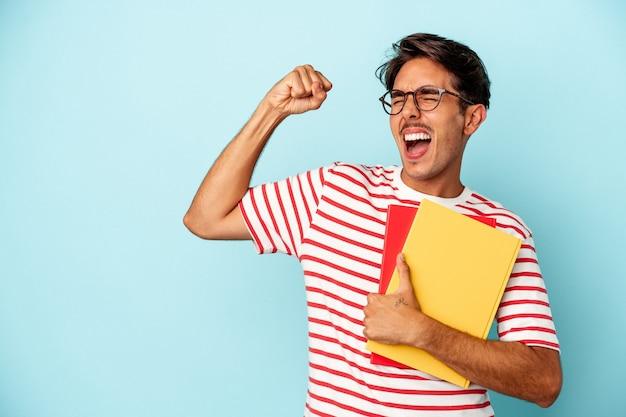 Giovane studente di razza mista che tiene in mano libri isolati su sfondo blu alzando il pugno dopo una vittoria, concetto di vincitore.