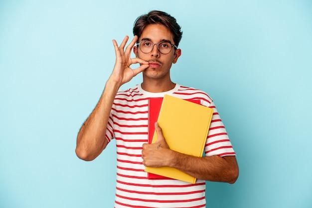 Giovane studente di razza mista che tiene libri isolati su sfondo blu con le dita sulle labbra mantenendo un segreto.