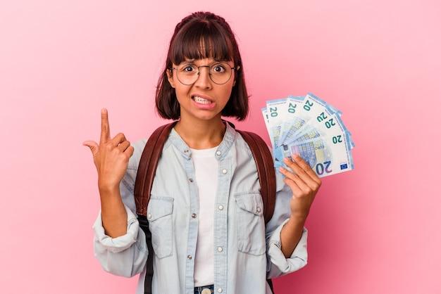Giovane studentessa di razza mista che tiene banconote isolate su sfondo rosa che mostra un gesto di delusione con l'indice.