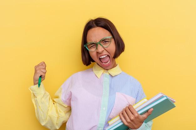 Donna giovane studente di razza mista isolata su sfondo giallo alzando il pugno dopo una vittoria, concetto di vincitore.