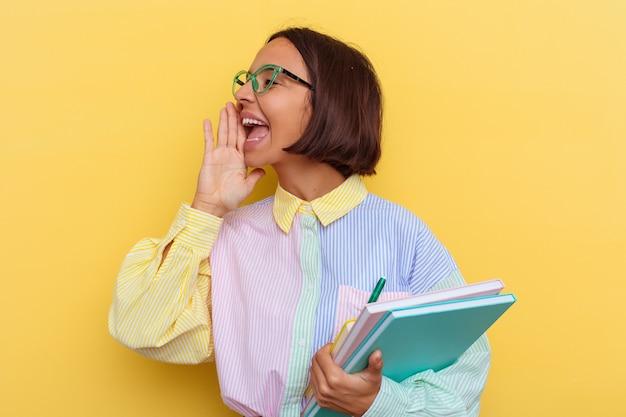 Giovane studentessa di razza mista isolata su sfondo giallo che grida e tiene il palmo vicino alla bocca aperta.