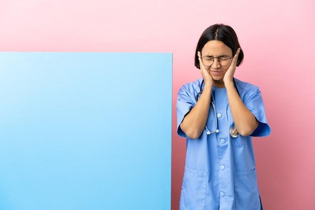 Giovane donna chirurgo di razza mista con un grande striscione su sfondo isolato frustrata e che copre le orecchie