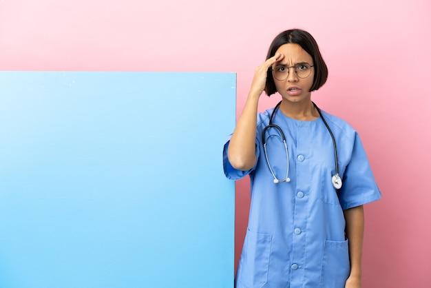 La giovane donna chirurgo di razza mista con un grande striscione su sfondo isolato ha realizzato qualcosa e intendeva la soluzione