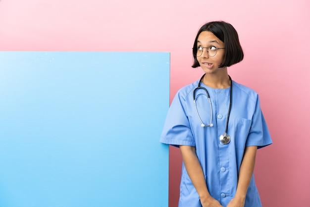 Giovane donna chirurgo di razza mista con un grande striscione su sfondo isolato che ha dubbi mentre guarda in alto