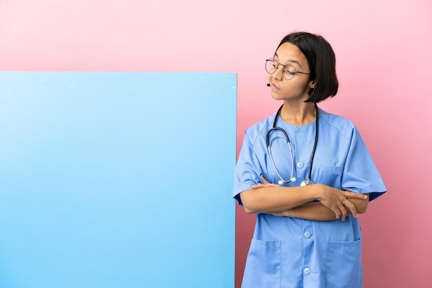 Giovane donna chirurgo di razza mista con un grande banner isolato sfondo e alzando lo sguardo looking