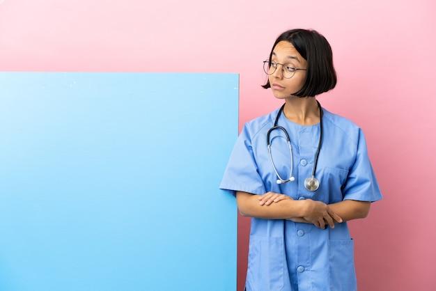 Giovane chirurgo di razza mista donna con un grande striscione su sfondo isolato facendo dubbi gesto guardando lato