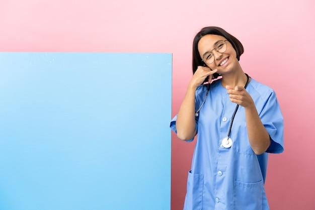 Giovane donna chirurgo di razza mista con un grande striscione su sfondo isolato che fa il gesto del telefono e punta davanti