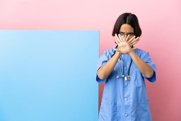 Giovane donna chirurgo di razza mista con un grande striscione su sfondo isolato che fa un gesto di arresto con la mano per fermare un atto