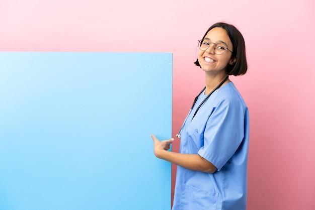 Giovane donna chirurgo di razza mista con un grande striscione su sfondo isolato che punta indietro