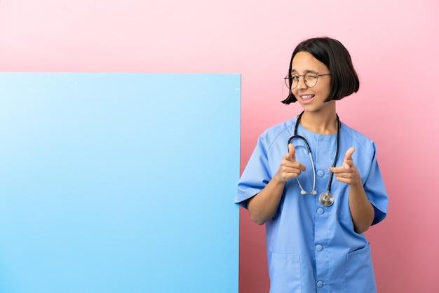Giovane donna chirurgo di razza mista con un grande striscione su sfondo isolato rivolto verso la parte anteriore e sorridente