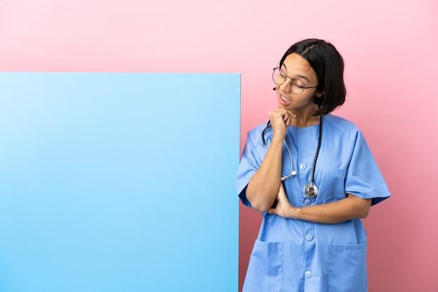 Giovane donna chirurgo di razza mista con un grande striscione sopra la parete isolata che osserva in su mentre sorride