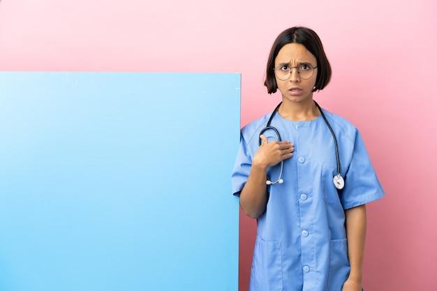 Giovane donna chirurgo di razza mista con un grande striscione sul muro isolato che punta a se stessi