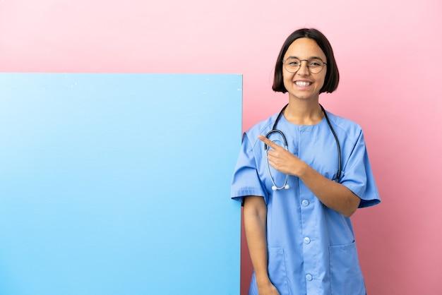 Giovane donna chirurgo di razza mista con un grande striscione sul muro isolato che punta di lato per presentare un prodotto