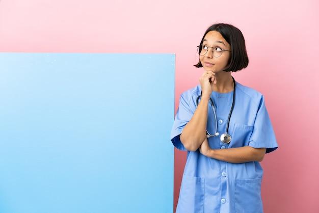 Giovane donna chirurgo di razza mista con un grande striscione sul muro isolato che pensa un'idea mentre guarda in alto