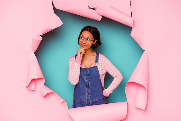 Giovane donna di razza mista dietro uno sfondo rotto scioccata che punta con l'indice a uno spazio di copia.