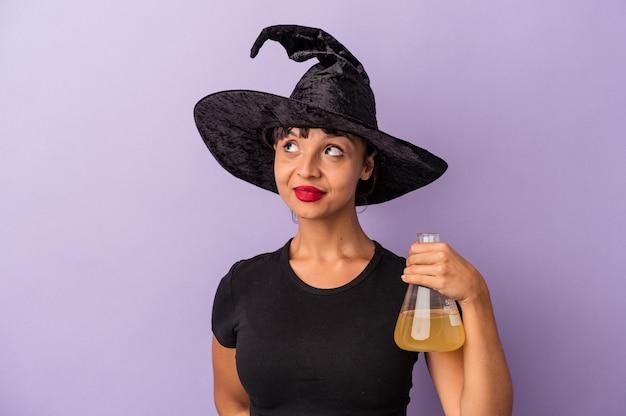 Giovane donna di razza mista travestita da strega che tiene pozione isolata su sfondo viola che sogna di raggiungere obiettivi e scopi